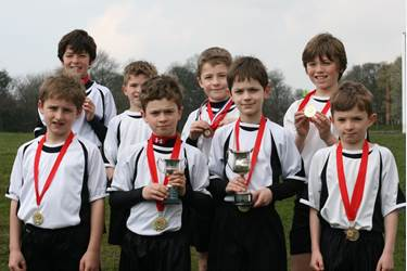 Runners from the Year 5 and Year 3/4 Bolton School Junior Boys' Cross Country team celebrate winning both team cups