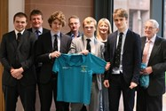 Mr J Flanagan, Mr G Flanagan and Mrs J Taylor present polo shirts to Mr Joseph, 1st XV coach and some of the players