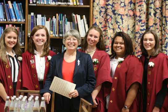 Old Girl, Professor Clack, is welcomed by the current Head Girl, Annabel Ault, and her deputies