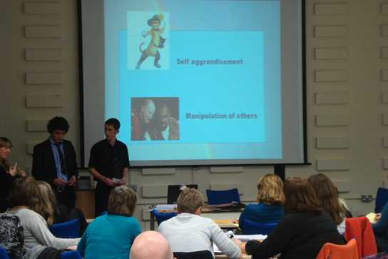 students presenting a project to a room of educational psychologists
