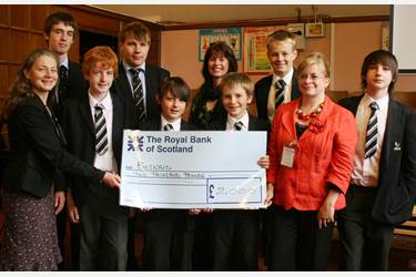 Members of the Halle Orchestra collect the cheque from the boys