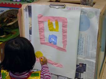 The children differentiate marks and movements on paper.