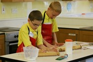 Two boys concentrate as they roll out their dough