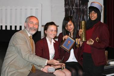 Professor Alexander shows some WWI artefacts to three Year 10 girls
