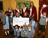 Phil Neville and his wife, Julie, happily collect the Bolton School cheque to help with The New Children
