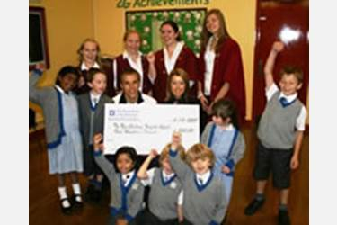 Phil Neville and his wife, Julie, happily collect the Bolton School cheque to help with The New Children's Hospital Appeal