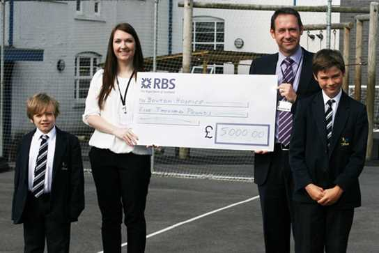 Mr Whittaker and two pupils present the cheque to Ms Lacaille