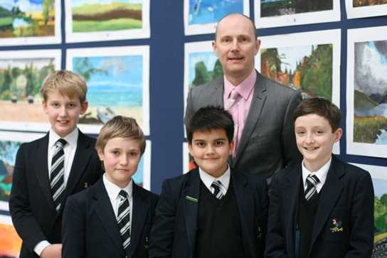 Mr Dickinson and the Art Committee show off the boys' acrylic landscape paintings