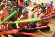 Year 5 pupils play percussion on boomwhackers