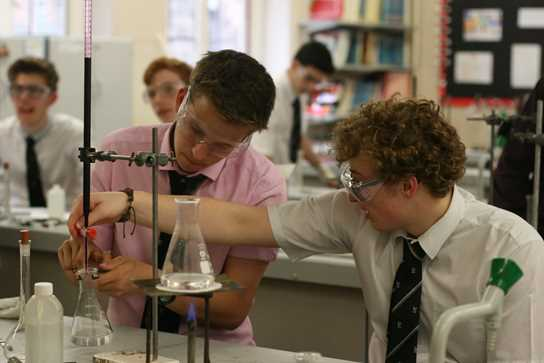 Two boys work together on the titrations