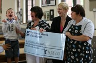 Reece and his mum receive the cheque from Catering Manager Karen Riley and Catering Supervisor Ronda Figgins