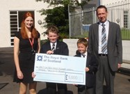 Jackie Pickersgill, Community Fundraiser for the Red Cross, receives the cheque from the boys