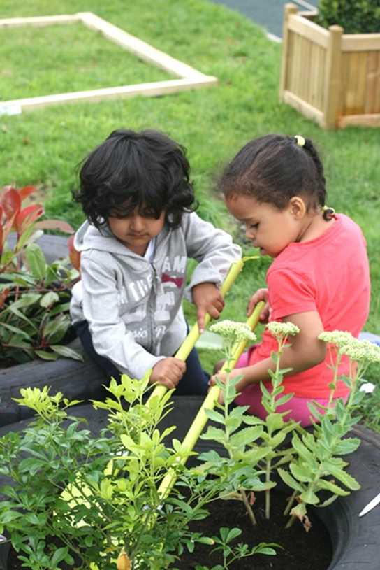 Two children add compost to a planting area