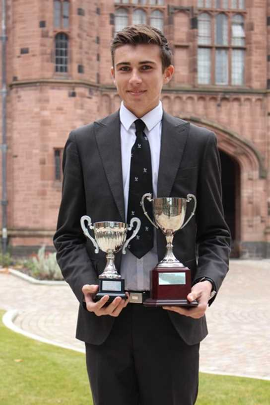 Year 13 pupil Benito O'Loughlin with the two trophies won by the Bolton School team