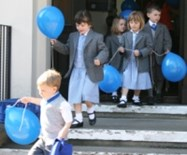 Pupils vacate the old Beech House for the very last time, carrying balloons and singing songs