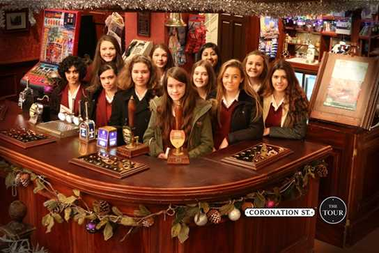 A group of girls pose behind the bar at the Rovers Return