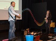 Demonstrating simple harmonic motion using a slinky, with reference to a guitar string