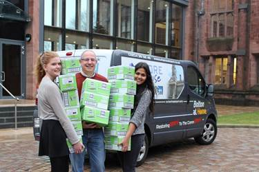 Lisa and Ananya with Dave Bagley carrying boxes of mints to the Urban Outreach van