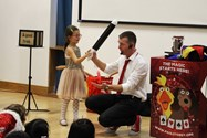 One of the girls helping Paul out with one of his magic tricks
