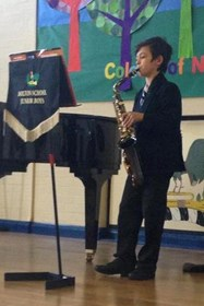 A young saxophonist takes the stage in the brass class