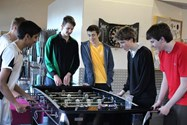 Boys playing a competitive game of table football