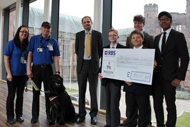 Tom Jones, Sam Bromley, Josh Fowler, Ilyas Ibrahim and the Headmaster present the cheque to Emma Allen-Taylor, Steve Cross and Guide Dog Nimmo