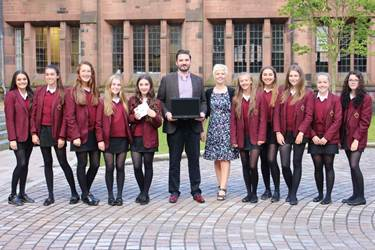 Ben Griffiths from Clever IT presents a laptop and projector to Mrs Crowther and the Bolton School girls