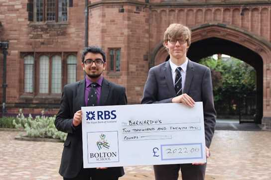 Year 12 pupils Samee Malik and Sam Gorick with the cheque for Barnardo's
