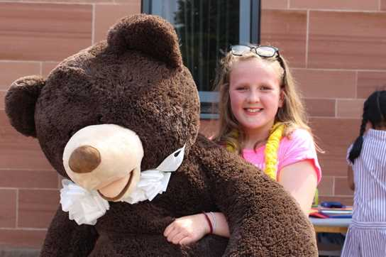 A girl carrying a prize from one of the raffles - a giant teddy!