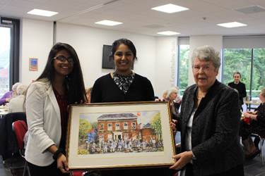 Shirley presents the painting to two delighted Sixth Form girls