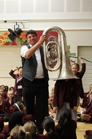 Chris demonstrates the large size of the Tuba