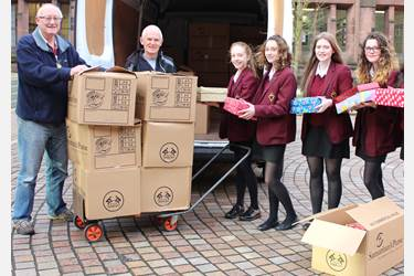 Girls help fill the van with Christmas shoeboxes