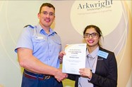 An RAF representative presents Khadijah with her award