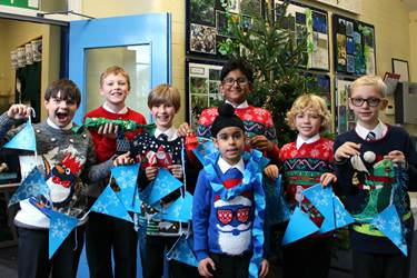 Some boys in Christmas jumpers with a selection of their hand-made decorations