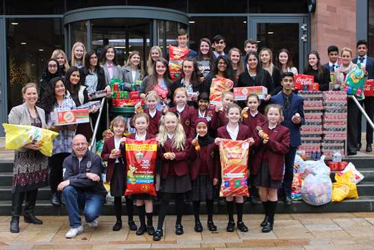 Sixth Form Girls and Boys and Junior Girls help load up the Urban Outreach van with crisps and pop for the Christmas hampers