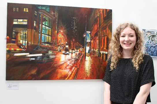 Nuala with her painting during an exhibit at Bolton University