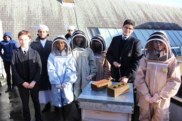 Members of the UTC Bolton Beekeeping Club are given beekeeping tips by Bolton School students
