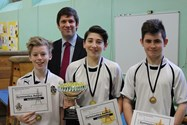 The three medallists are congratulated by Mr Ford, Assistant Headmaster