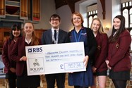 Year 10 girls and Mr Winrow, Y10 Tutor, hand over a cheque to Manchester Children