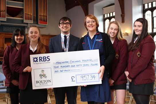 Year 10 girls and Mr Winrow, Y10 Tutor, hand over a cheque to Manchester Children's Hospital
