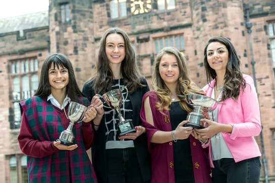 Four individual senior sports prize winners, Priya, Amelia, Georgia and Hannah, show off their trophies.