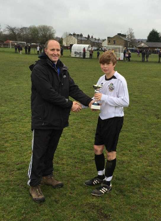 Captain William Jackson lifts the cup on behalf of the U13s