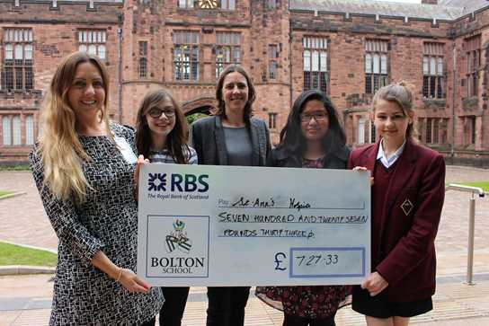 Charity Prefects Emma Hussain, Abbie Humphrey and Tayyibah Khalid hand over  a cheque to Hannah Saunders, Partnerships Manager at St Ann's Hospice