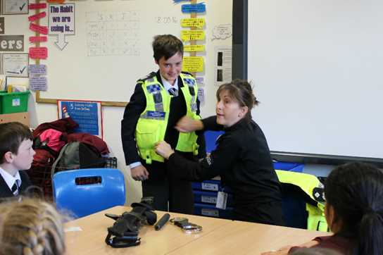 A pupil demonstrates some of the gear a police officer wears in Janette's session