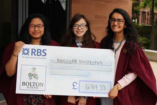Abbie, Emma and Tayyibah hand over a cheque for Muscular Dystrophy UK