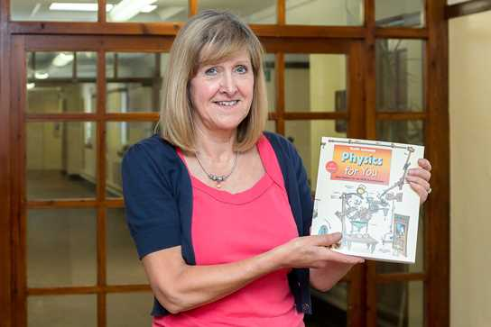 Mrs Holt shows off the fifth edition of Physics for You