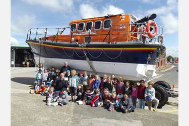 The children hand over their cheque to the RNLI