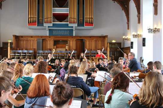 A full orchestra rehearsal in the Girls' Division Great Hall
