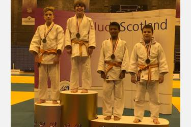 Jamie is pictured here second left on the podium. He is an orange belt (8th Mon)
