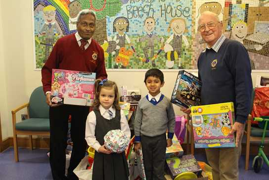Olivia and Umar, Year 1 pupils, help hand over gifts to Babu Roye and Bill Laithwaite of Bolton Lions